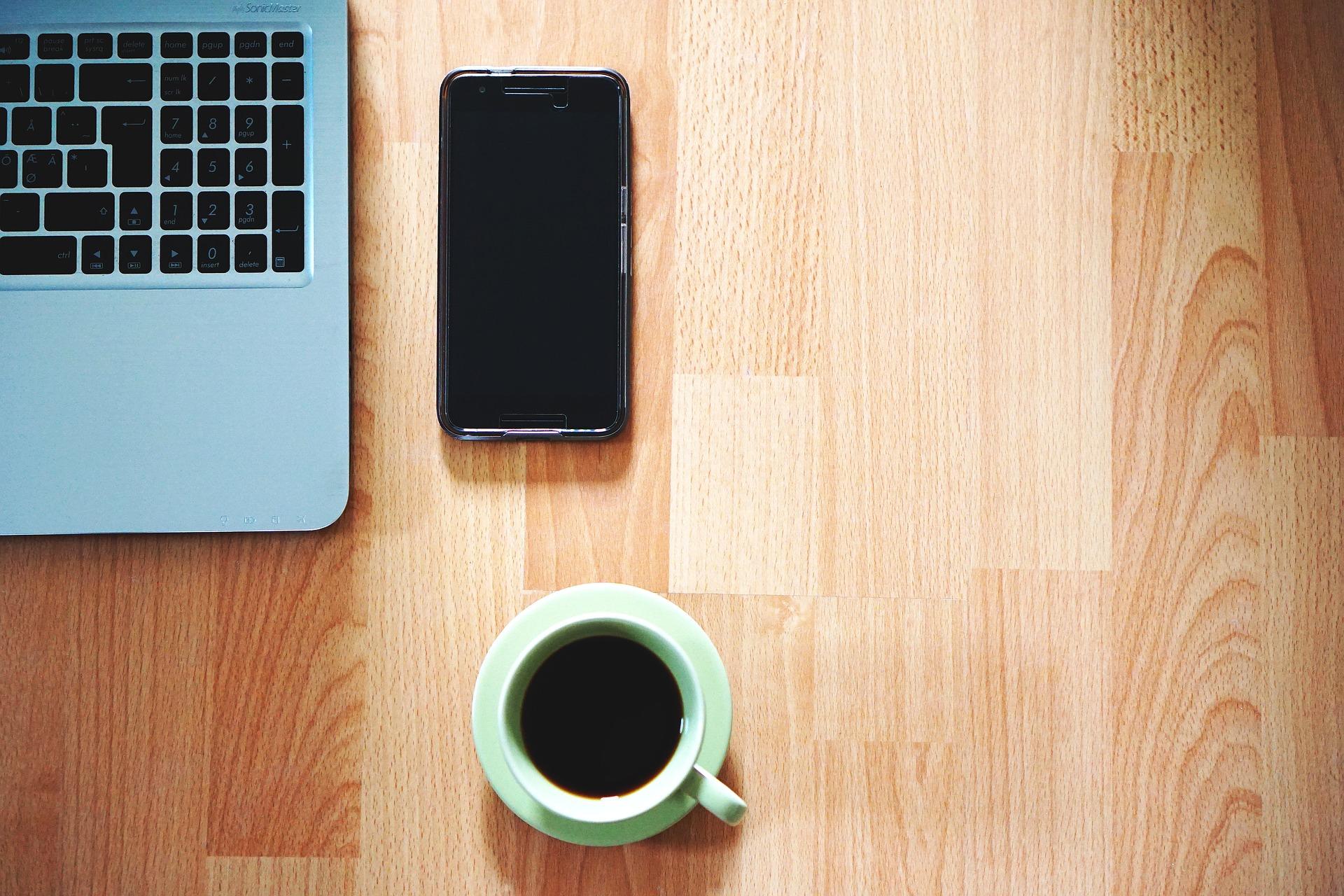 デスクに置かれたパソコンとスマホとコーヒー