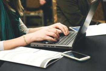 ノートパソコンで作業する人の画像